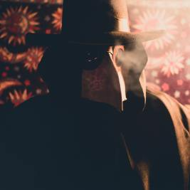 person-in-black-coat-and-hat-with-plague-doctor-mask-1607862