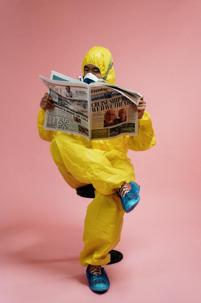 man-in-yellow-protective-suit-holding-a-newspaper-3951350
