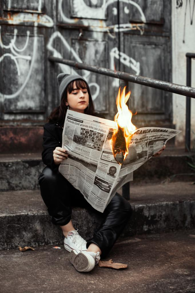 woman-holding-newspaper-while-burning-3422053
